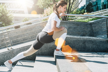 Sunny summer day. Young woman in sportswear doing stretching exercises outdoor. Girl doing warm-up on steps before training. Exercise in street, sports exercises, workout.