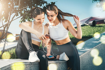 Two young women athletes in sportswear are sitting in park, relax after sports training, use smartphone, listening to music. Girl shows her friend photos on smartphone screen. Online training.