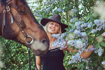 A charming woman riding a brown horse.
