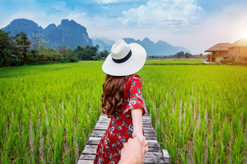 Wall Mural - Woman holding man's hand and leading him to Wooden path and green rice field in Vang Vieng, Laos.