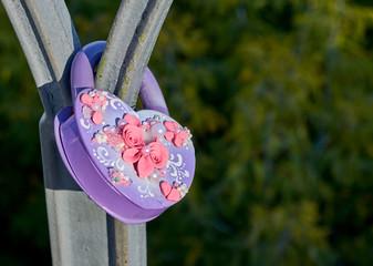 Purple wedding lock shape of a heart on the metall bridge