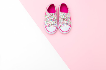 Sneakers for baby on a white and pink background. Flat lay