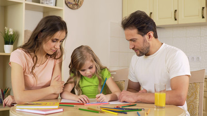 Friendly family sitting in kitchen drawing pictures, enjoying leisure together