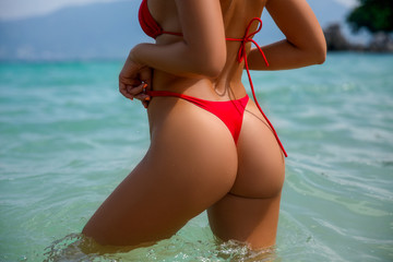 Ideal woman's butt and hips - perfect anti-cellulite and skin care therapy program. Ocean beach photo.