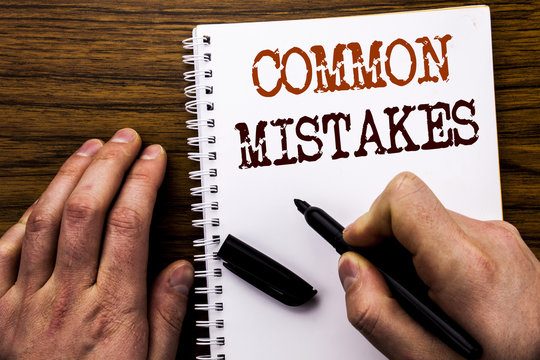 Handwritten text showing word Common Mistakes. Business concept for Common Concept Written on tablet laptop, wooden background with businessman hand, finger writing on notebook book.