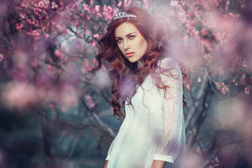 Beautiful young woman in pink peach garden. Fashion concept