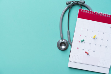 Top view of stethoscope and calendar on the green background, schedule to check up healthy concept