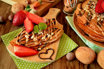 Crepes decorated with nuts, chocolate, fresh strawberries and mint served on a wooden table