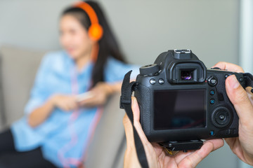 Close up man hands holding digital camera taking photo of model woman.