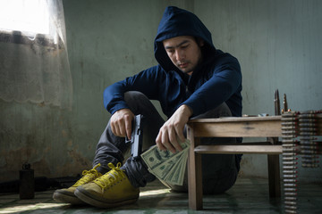 Terrorist sitting in dark and dirty room feeling despair, depressed and sad thinking about bad things. Young hopeless man hands holding gun and money. Drug dealer,criminal with weapons concept.