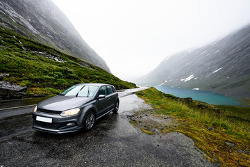 Grey modern car is parking next to a rural road in a valley surrounded by a fjord and snow covered mountains on a rainy day in Norway.