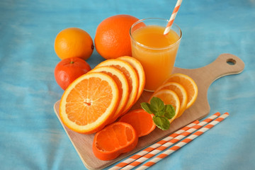 Slices of orange, mandarin and lemon and yellow juice in a glass on blue background