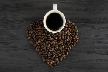 A cup of coffee and fried coffee beans in the form of a heart on a black wooden background.