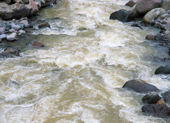 Mountain river with stones. Fast water current. Water photo texture.