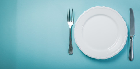 Intermittent fastin concept - empty plate on blue background Wall mural