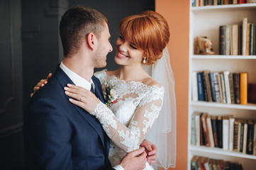 The bride in a lace dress smiles happily. The newlyweds look at each other gently. The red-haired bride.