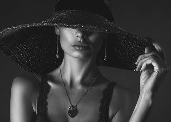 beautiful girl close-up, in underwear and hat on black background, black and white photo