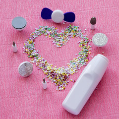 Manicure background with accessories for milling cutter and heart shape of colorful foils.