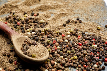 Top view on composition of peppercorns in wooden spoon on dark background, close-up.
