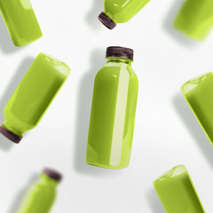 Green smoothie or juice bottles pattern on white background, top view, flat lay. Branding copy space