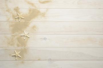Conchas, estrellas de mar y caracolas marinas sobre fondo de madera blanca con arena
