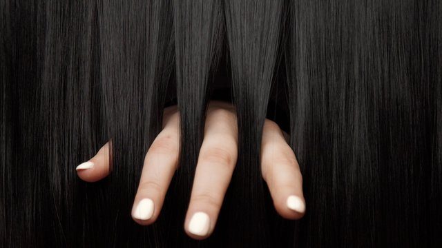 Hair texture background, no person. Black shiny hair Hands touching it fingers throught the hair