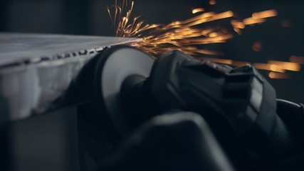 Worker using industrial grinder. Worker in garage makes work with metall and grinder. many bright flying sparks