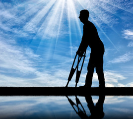 Silhouette of a disabled man with crutches walking near the river with his reflection