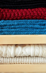 Knitted clothes are piled carefully on wooden shelves