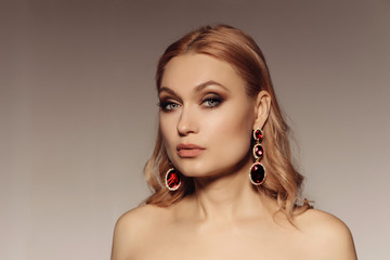 Elegant portrait of a middle-aged woman with big earrings with red stones. Gorgeous luxury statement accessory