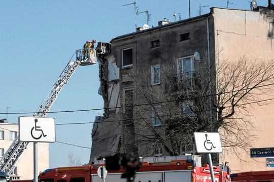 Firemen work on site of a partially collapsed apartment building after a gas explosion in Poznan