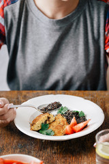 Woman eating vegetarian food (black quinoa and cutlets from oatmeal and prunes). Healthy vegetarian food concept