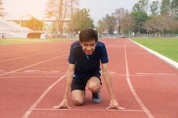 Asian man ready start run on track stadium