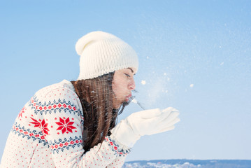 girl in a white winter sweater blows on the snow, flies in the wind