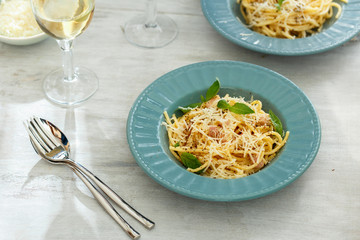 Plate of spaghetti carbonara with glass of white wine on white wooden table. Dinner table concept