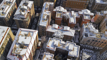 Aerial view of a group of buildings in the residential district of an Italian city. Snow and ice cover the roof of the houses and the square in front of the cars on this cold winter day.