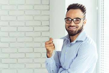 Relaxed black businessman in office, drink coffee