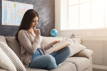 Young thoughtful woman reading book