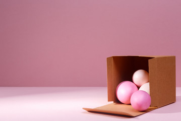 Eggs falling out of the craft cardboard box. Creative Easter concept. Modern solid background