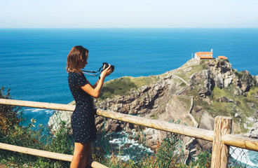 Tourist traveler photographer making pictures sea scape on photo camera on background ocean gaztelugatxe steps on Spain, hipster girl looking on nature horizon, relax holiday