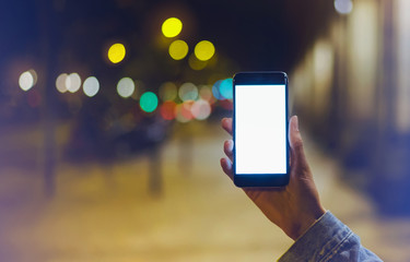 hipster using in hands clean gadget mobile phone closeup, blogger pointing finger on blank screen smartphone on background bokeh light in night atmospheric city, mockup online wifi internet concept