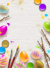 Easter background with space for greeting or message. Pussy-willow branches, paint decorated multicolored eggs on a wooden desktop.