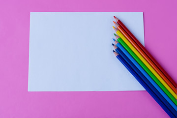 Colorful pencils and paper on pink background. Space for text