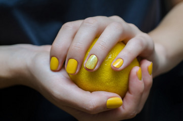 Female hands withyellow nail design.