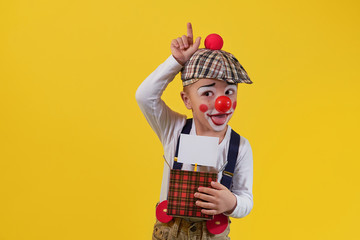 Cute little boy clown in a costume, makeup.Funny kid clown fooling.Young child shows expression face joy,smile,cheerful.1 April fool's day celebration.Concept holiday, birthday,laughter,jokes,party.
