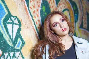 teenager beautiful redhead hispanic girl posing by a wall with colorful graffiti, urban style with casual and modern clothes