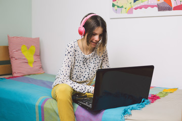 Teenage girl sitting bed and using laptop at her home