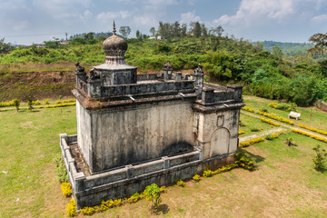 Madikeri, India - October 31, 2013: Closeup on small white and gray Guru Rudrappa mausoleum with bull statue on top, set in green garden of domain Raja Tombs. Shot form roof.