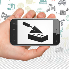 Constructing concept: Hand Holding Smartphone with  black Brick Wall icon on display,  Hand Drawn Building Icons background, 3D rendering