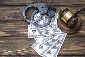 handcuffs with hammer of judge and one hundred dollar money banknotes. crime and punishment. court.